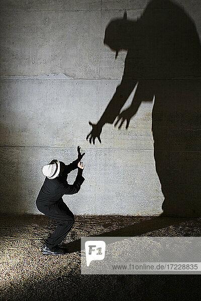 Mann kauert vor großem  bedrohlichem Schatten an der Wand
