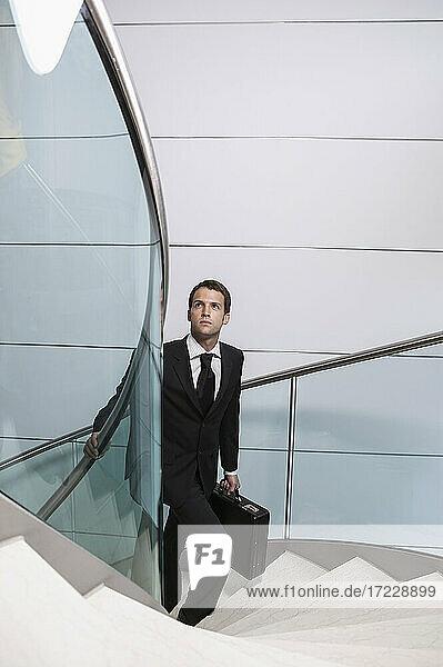Geschäftsmann mit Aktentasche blickt nach oben steigende Wendeltreppe