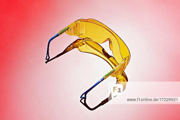 Gelbe Schutzbrille auf rotem Hintergrund
