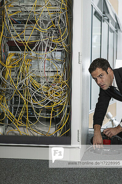 Porträt eines verdächtigen Geschäftsmannes  der den Stecker des Netzwerkservers aussteckt