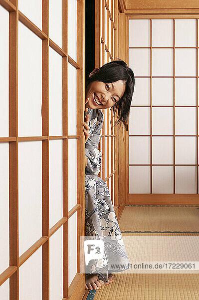 Porträt glückliche verspielte junge Frau in Kimono späht aus hinter shoji Tür