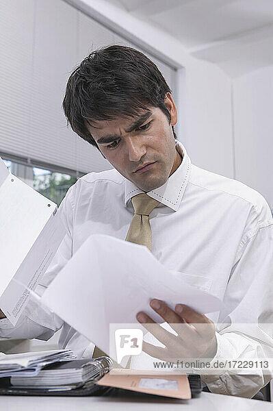 Verwirrter Geschäftsmann beim Durchsehen von Papierkram im Büro