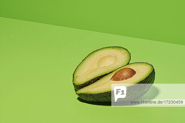 Halbierte Avocado auf hellgrünem Untergrund