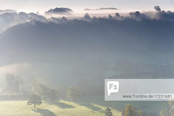 Blick über das Dorf Uley in den Cotswolds  Nebel und Wolken.