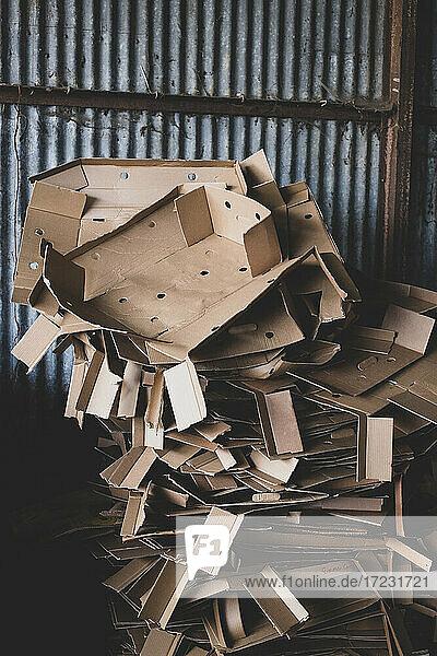 Nahaufnahme eines Haufens zerknitterter Pappkartons auf einem Bauernhof.