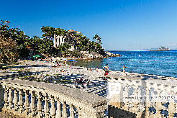 People on the beach and the terrace of a traditional villa  Cavo