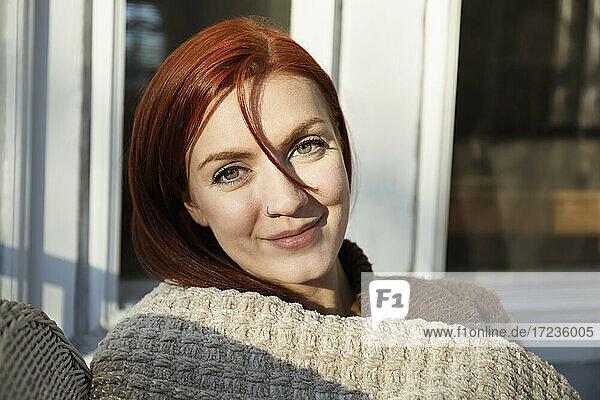 Porträt einer jungen Frau mit roten Haaren auf einer Veranda