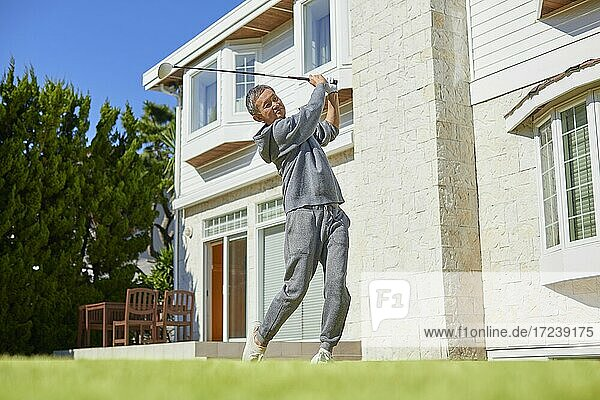 Senior Japanese man playing golf at home