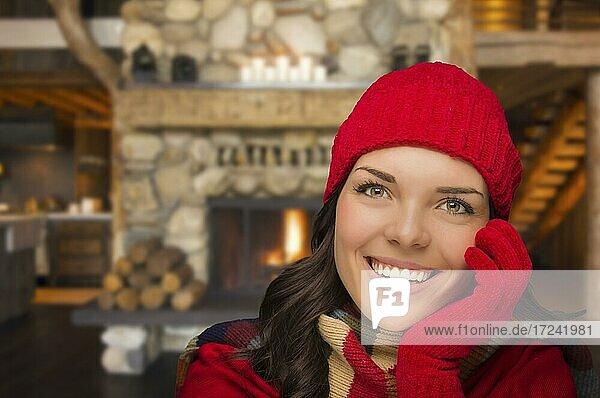 Smiling  comfortable mixed race girl looking at camera enjoying warm fireplace in rustic cabin