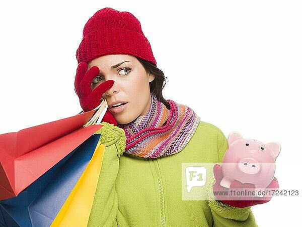 Concerned expressive mixed-race woman wearing winter clothing holding shopping bags and piggybank isolated on white background