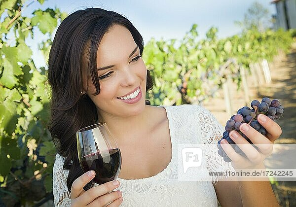 Pretty mixed race young adult woman enjoying A glass of wine in the vineyard