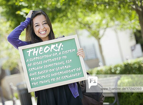 Excited mixed race female student holding chalkboard with theory and the definition written on it