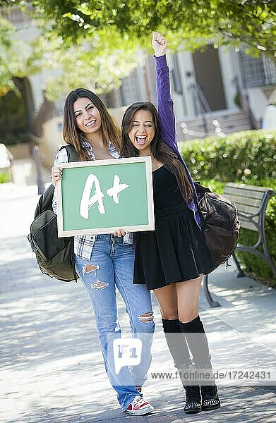 Excited mixed race female students holding chalkboard with A+ written on it