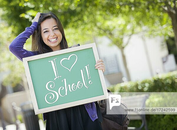 Excited mixed race female student holding a chalkboard with I love school written on it