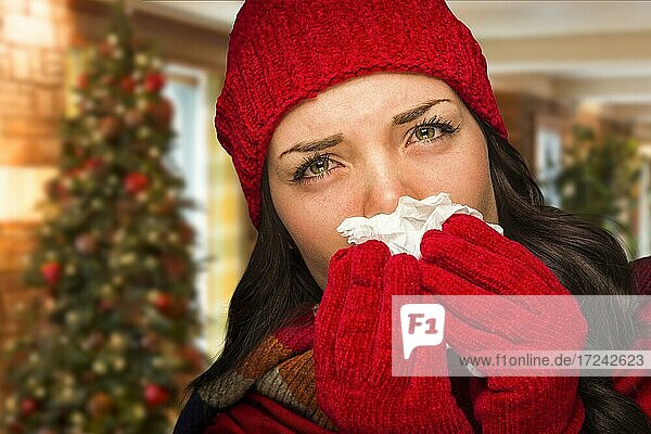 Sick mixed race woman blowing her sore nose with tissue in christmas setting