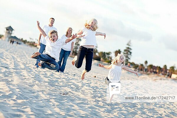 Happy sibling children jumping for joy at the beach as parents watch