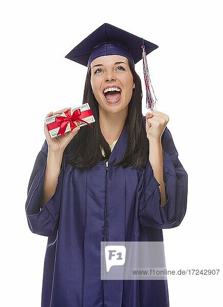 Happy female graduate in cap and gown holding stack of gift wrapped hundred dollar bills isolated on a white background