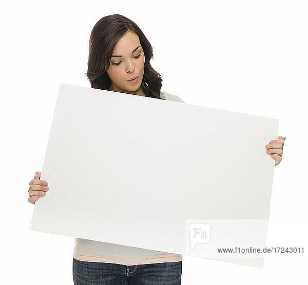 Beautiful mixed-race female holding and looking at blank sign isolated on a white background