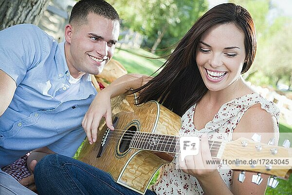 Happy mixed-race couple at the park playing guitar and singing songs