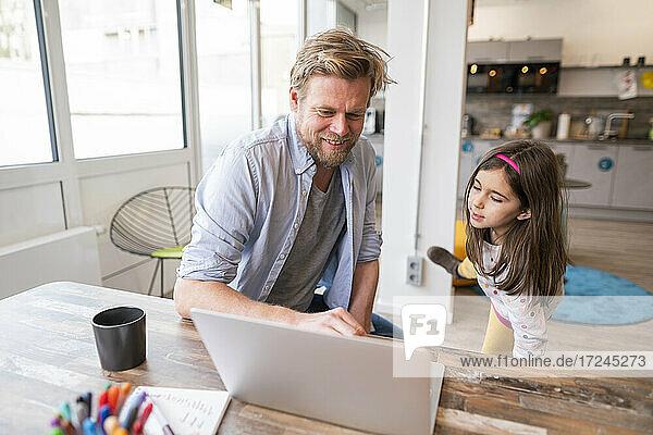 Lächelnder Vater unterrichtet seine Tochter zu Hause am Laptop