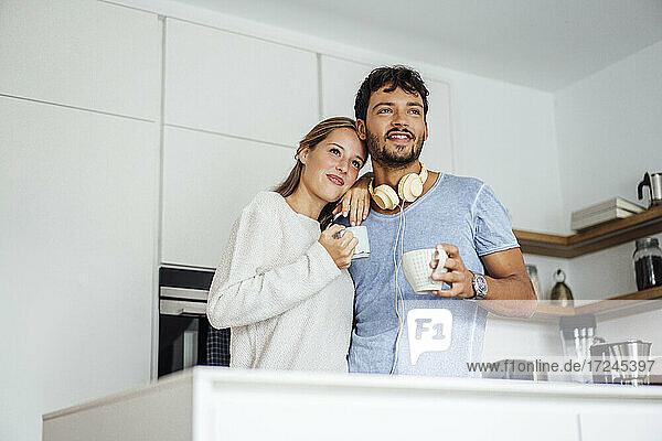 Lächelndes junges Paar hält Kaffeetasse in der Küche und schaut weg
