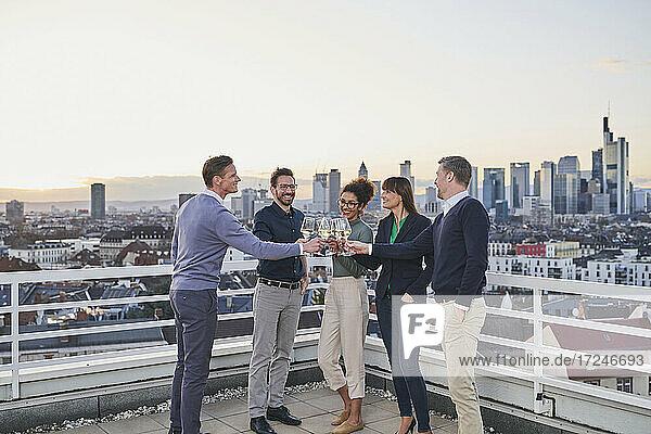Unternehmer stoßen mit Weingläsern an  während sie auf dem Dach stehen