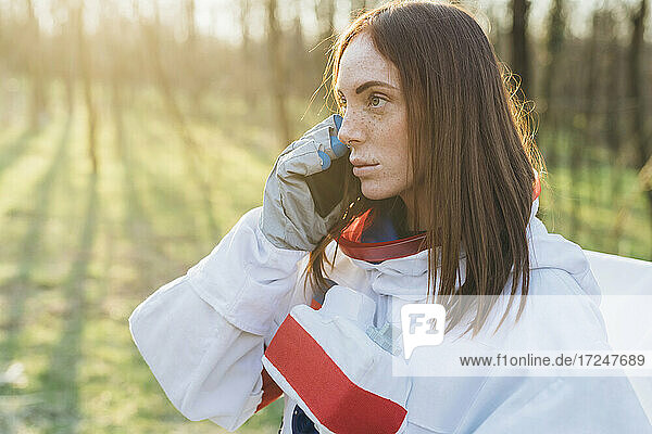 Young female explorer talking on mobile phone during sunny day