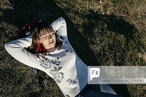 Young woman with hands behind head lying on grass