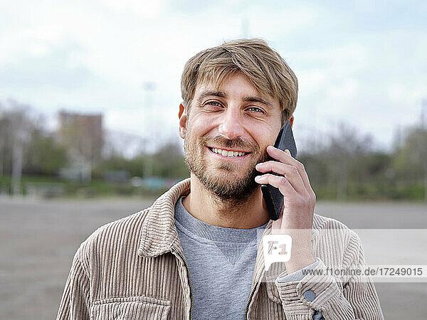 Smiling handsome man talking on mobile phone