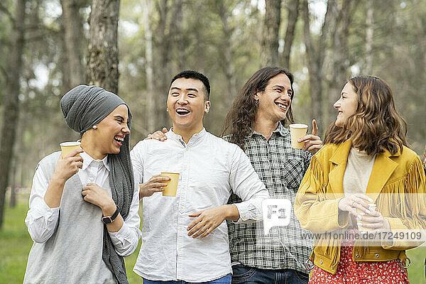 Männliche und weibliche Freunde halten ein Glas und genießen es im Wald