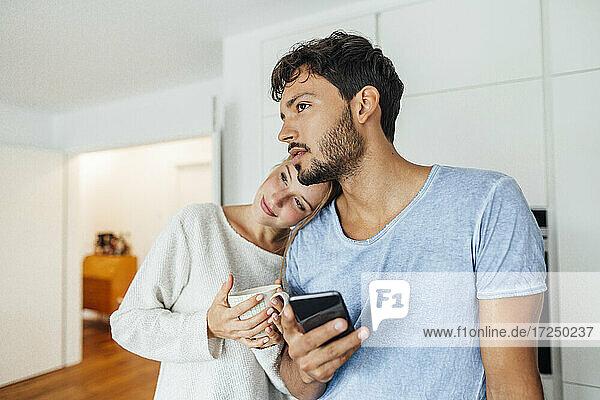 Junger Mann mit Smartphone steht neben seiner Freundin und schaut weg