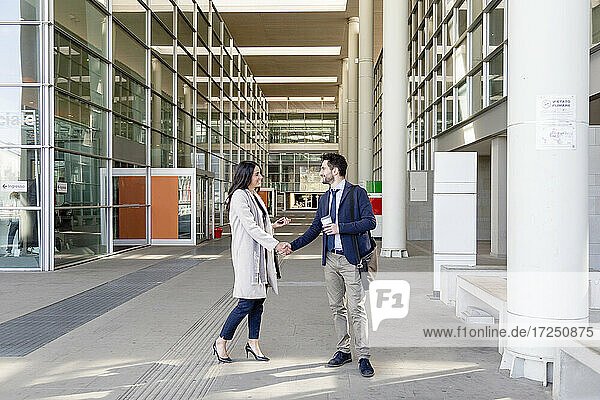 Geschäftsleute grüßen sich per Handschlag  während sie auf dem Fußweg stehen
