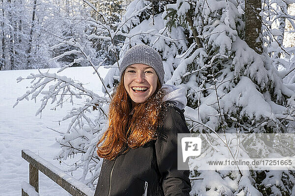 Happy woman with red hair in front of snow covered tree during winter