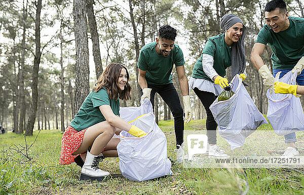Mitarbeiter von Wohlfahrtsverbänden und Hilfsorganisationen sammeln im Wald Müll in Plastiksäcken