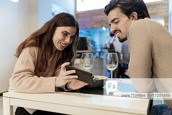Lächelnde junge Frau zeigt ihrem Freund im Restaurant ihr Smartphone