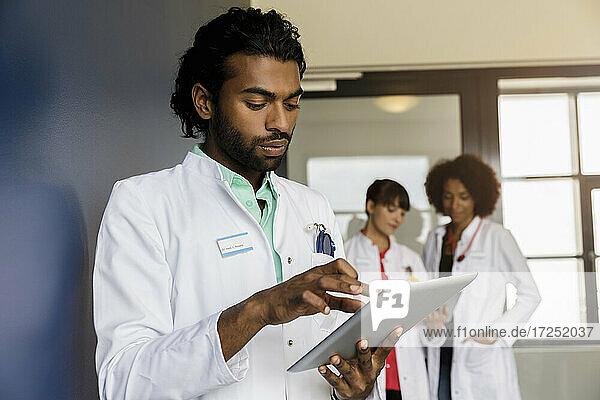 Junge männliche Mitarbeiter im Gesundheitswesen  die ein digitales Tablet benutzen  mit weiblichen Kollegen im Hintergrund im Krankenhaus