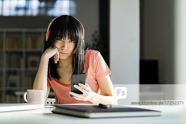 Frau mit Kopfhörern hält Smartphone  während sie zu Hause auf dem Tisch sitzt