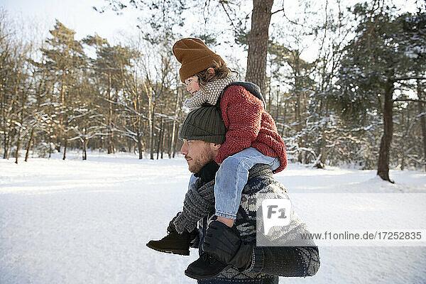 Vater hält seinen Sohn auf der Schulter sitzend im Winter