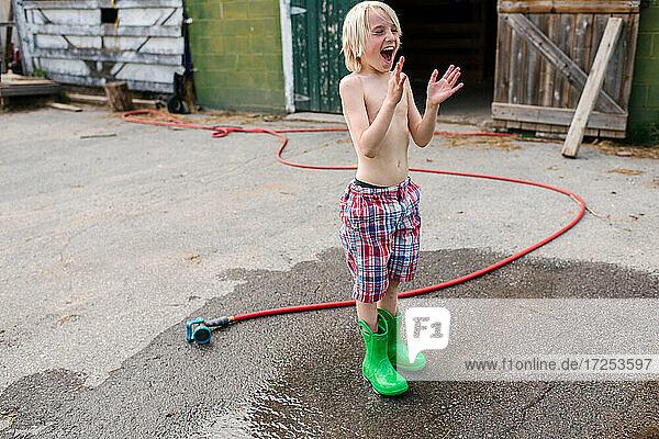 Canada  Ontario  Kingston  Shirtless boy playing with gardening hose