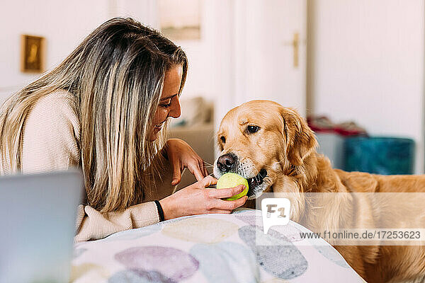 Italy  Young woman and dog playing at home