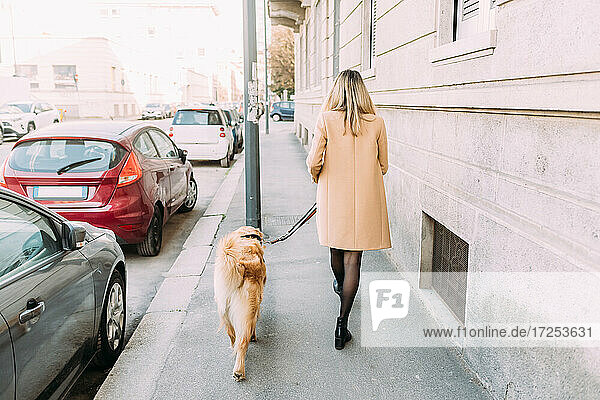 Italy  Young woman and dog walking along street