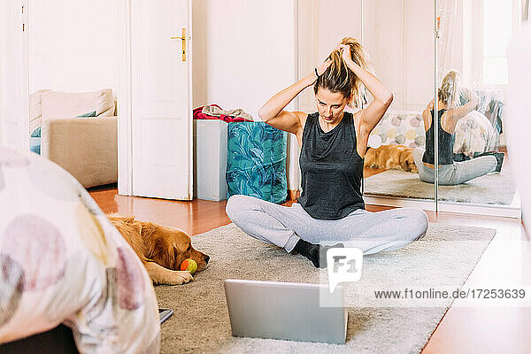 Italy  Young woman stretching in front of laptop on floor