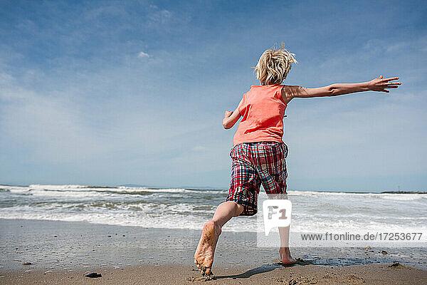 USA  California  Ventura  Rear view of boy running on beach