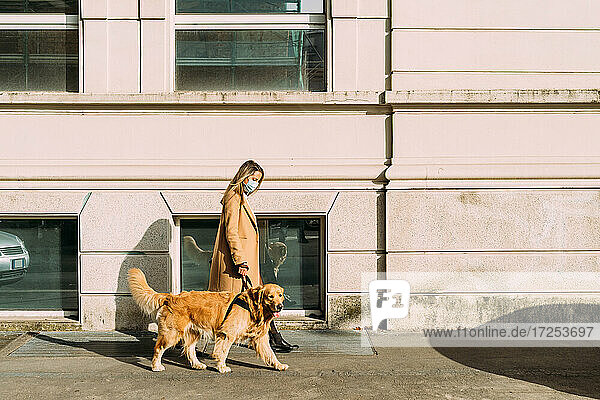 Italy  Woman with dog walking along street