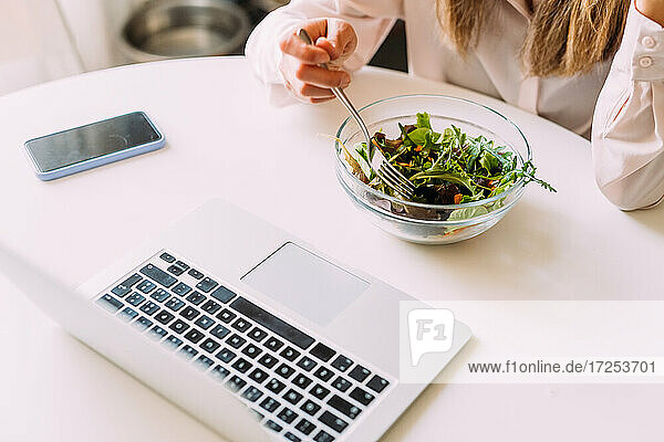 Italy  Woman eating salad and looking at laptop