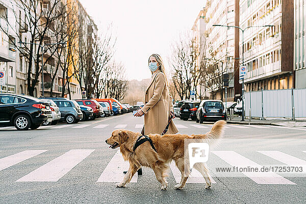 Italy  Woman with dog walking across street