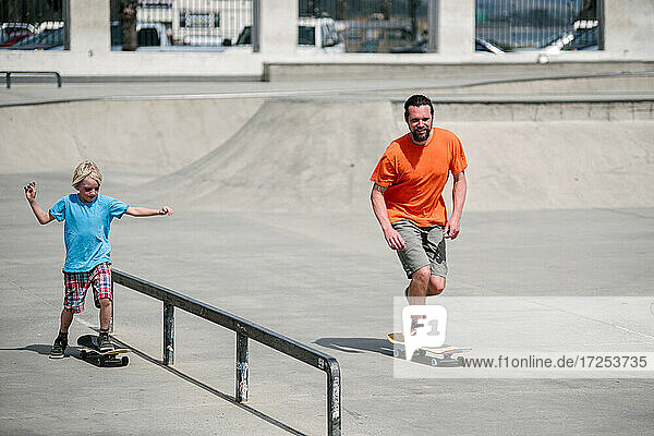 USA  California  Ventura  Father and son skateboarding in skate park