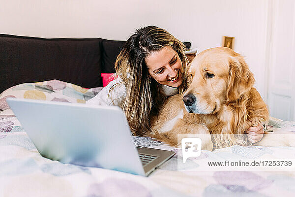 Italy  Young woman with dog on bed looking at laptop