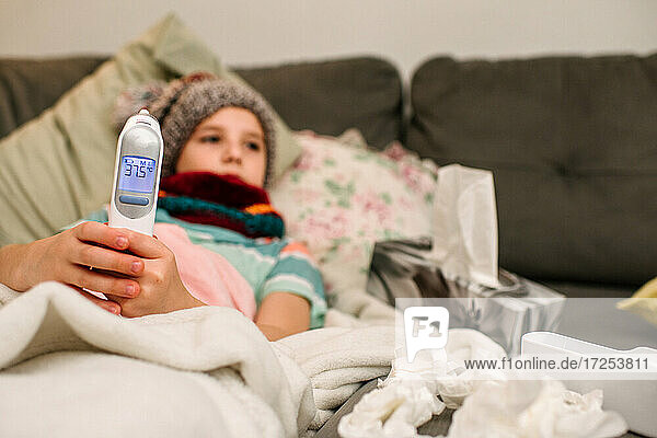 Canada  Ontario  Boy in knit hat holding electronic thermometer on sofa