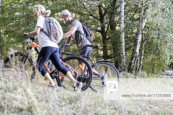 Mature couple with bicycles walking in forest